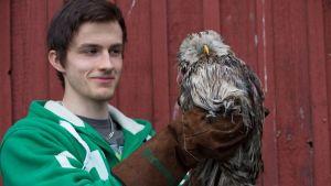 Heinolan lintutarhalla mies ja pöllö.