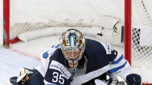 Pekka Rinne sulkee kiekkoa itselleen.