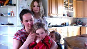 Kunniamerkillä palkittu äiti Anu Salo kolmen lapsensa ympäroimänä.