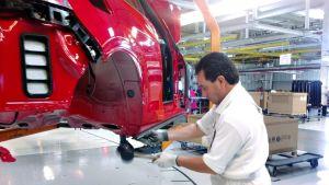 Mies työskentelee autotehtassa.