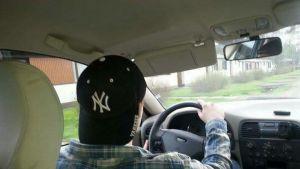 Nuori mies ajaa autoa lippis väärinpäin päässä