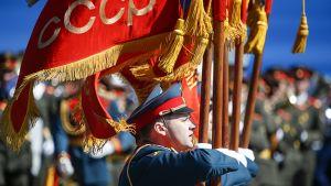 sotilas kantaa lippua paraatissa