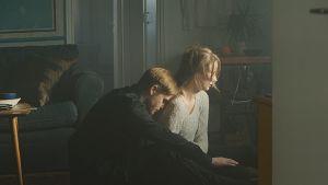Mies nojaa harmaaneuleisen naisen selkää vasten olohuoneessa.