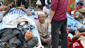 Maanjäristyksen uhreja makaa sängyillä avoimella alueella.
