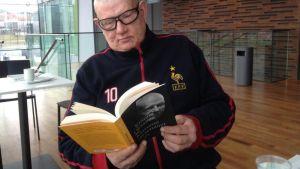 Kimmo Oksanen selaa kirjaa.