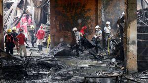 Filippiiniläiset poliisit etsivät ruumiita kenkätehtaan raunioista Manilassa.