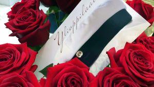 Onnittelukortti ylioppilaalle ruusujen ympäröimänä.