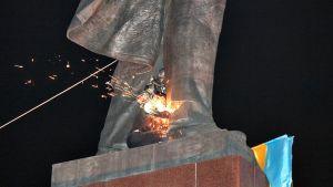 Mielenosoittajat leikkaa Vladimir Lenin patsaan jalkoja poikki Harkovassa.