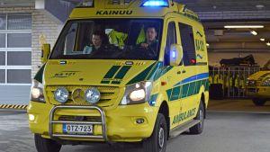 Ambulanssi lähtee liikenteeseen sairaalan parkkihallista.