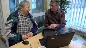Kaksi miestä käyttää tietokonetta ja tablettia.