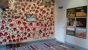 Kuvassa värikäs huoneen nurkkaus, räsymatto, kukallinen tapetti, taulukokoelma seinällä.