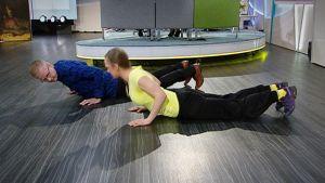 Personal trainer Mari Putus ja toimittaja Juha Hietanen punnertavat studion lattialla.
