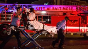 Pelastustyöntekijät kuljettavat hoidettavaksi mielenosoittajaa, jota poliisit suihkuttivat kasvoihin pippurisuihkeella Freddie Grayn kuoleman nostattamassa mellakassa Baltimoressa 2. toukokuuta.