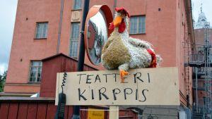 Kuvassa kananukke on asetettu kyltin päälle houkuttelemaan ihmisiä teatterikirppikselle.
