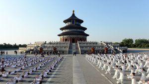 Sadat ihmiset venyttelevät tempelin edessä.