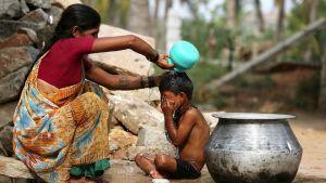 Äiti jäähdyttelee lastansa piinaavan helteen aikana.