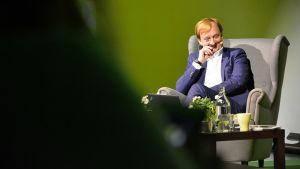 Hymyilevä Hjallis Harkimo istuu nojatuolissa yleisön edessä.