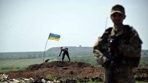 Ukrainalainen sotilas seisoo etualalla vartiossa, kun toinen sotilas taaempana kaivaa valliestettä 26. toukokuuta.