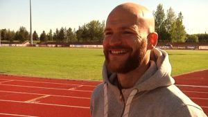 Mies hymyilee leveöästi. Taustalla jalkapallokenttä.