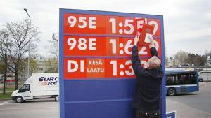 Mies vaihtaa numeroita hintatauluun huoltoasemalla.