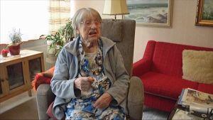 Irja Remmi viittomassa olohuoneessaan.