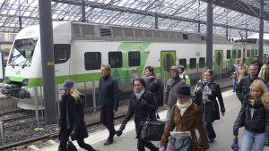 Matkustajia kävelemässä rautaieaseman laiturilla.