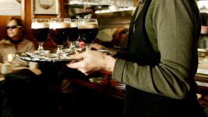 Tarjoilija kantaa tarjontinta ravintolassa.