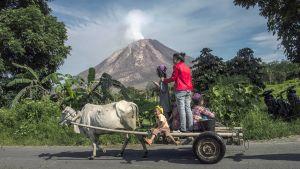 Indonesialainen perhe ohittaa Sinabungin tuolivuoren Karossa