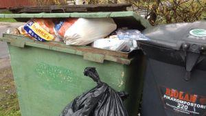 Ylitsepursuava roskalaatikko, jätesäkki maassa.
