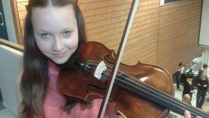 Kuvassa viulua soittava tyttö katsoo kameraan.