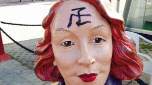 Naista esittävän patsaan otsaan on töherretty mustalla tussilla hakaristiä muistuttava kuvio.