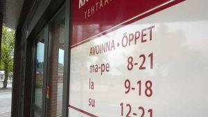Kuvassa punavalkoinen kauppakeskuksen kyltti, joka kertoo aukioloajat.