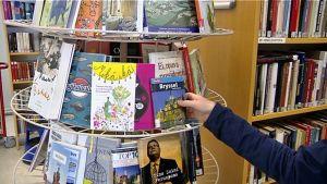 Henkilö ottaa kirjaa kirjaston hyllystä.