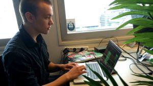 Niilo Kämäräinen työskentelee tietokoneella.