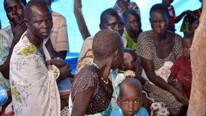 Eteläsudanilaisia taistelujen tieltä pakoon lähteneitä naisia istuskelee teltan suojassa.