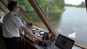Laivan kapteeni ohjaa laivaa kapeassa kohdassa Vanajavedellä.
