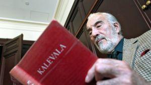 Englantilainen näyttelijä Christopher Lee lukee punakantista Kalevalaa.