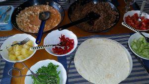 Kuvassa tortilla-aineksia kupeissa  ananaspaloja, pannussa broileria, vihanneksia ja tortillapohjia.