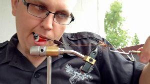 Juha Poukarilla toimii vain vasen käsi. Hän käyttää perhonsidonnassa apuna suutaan.