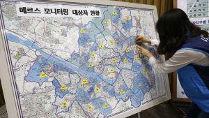 Virkamies merkitsee Soulin karttaan ilmeneviä MERS tapauksia.