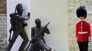 Brittisotilas punaisessa univormussa ja karvalakissa vartioi patsasta, joka esittää kahta 1800-luvun sotilasta.