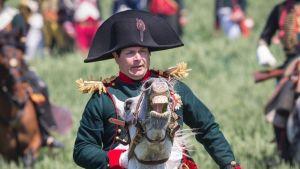Ranskalainen näyttelijä Frank Simson hirnuvan hevosen selässä eli Napoleonina Waterloon taisteluesityksessä Lignyssa Belgiassa kesäkuussa 2015