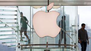 Applen logona takana on portaikko, jossa kävelee ihmisiä.
