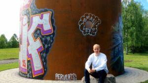 Taiteilija Joonas Mikola istuu teräslieriön edessä, johon on maalattu graffiteja.