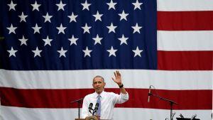 Barack Obama suuren Yhdysvaltain lipun edessä.