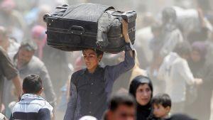 Pakolaisia, joista yhden pään päällä suuri matkalaukku