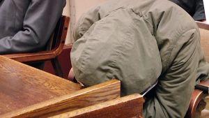 Mies on vetänyt vihreän maiharin hupun kasvojensa suojaksi ja nojaa päätään oikeussalin pöytään.