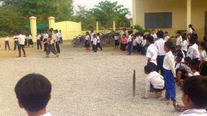 Koululaiset pelaavat pesäpalloa.