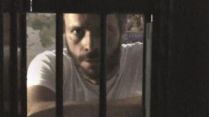 Mies katsoo kameraa vankilakaltereiden takaa.