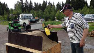 Rake Leino valmistelee hiekkaveistostaan kastelemalla hiekkaa.